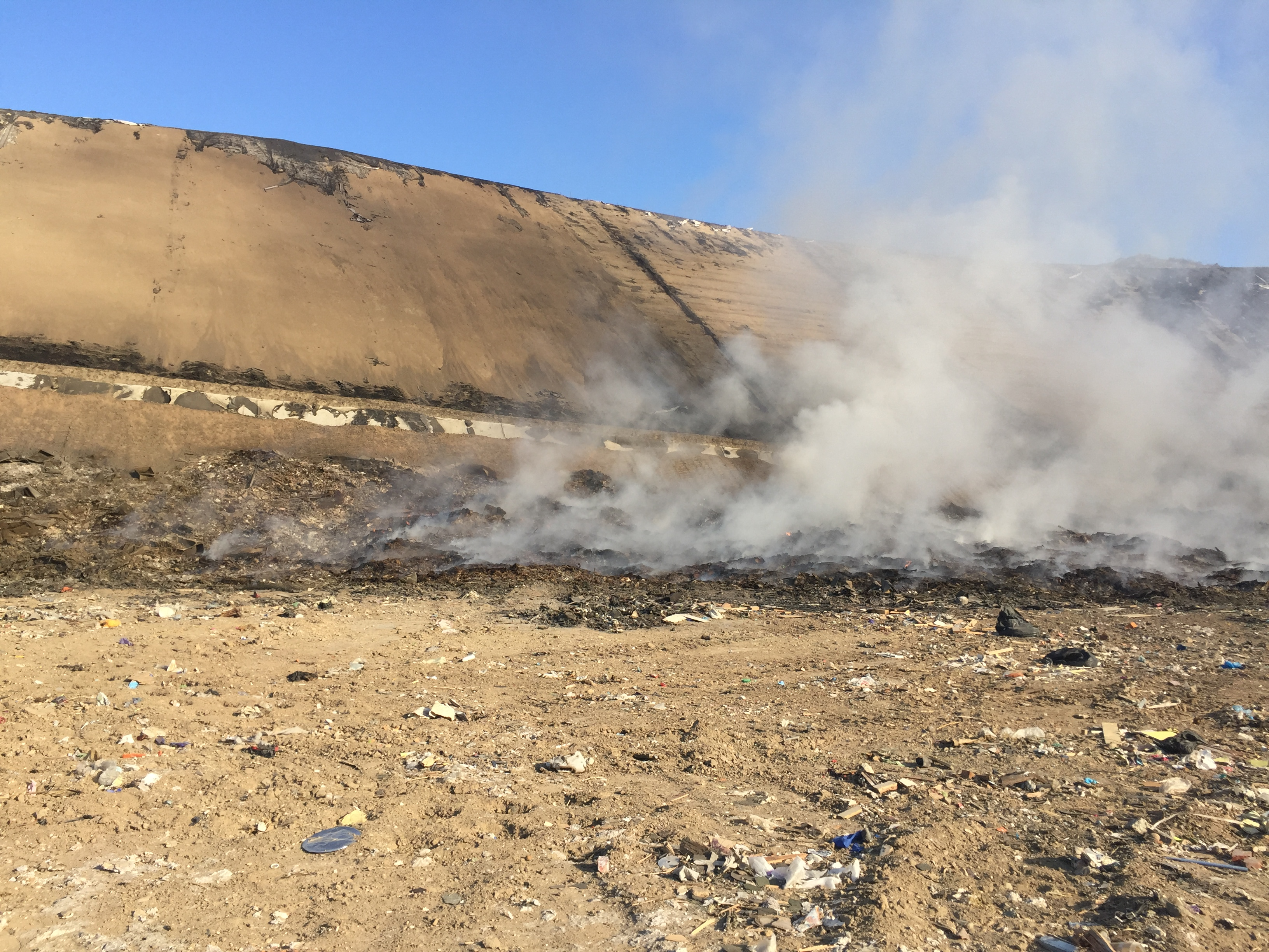 Damaged liner at the landfill with smoke