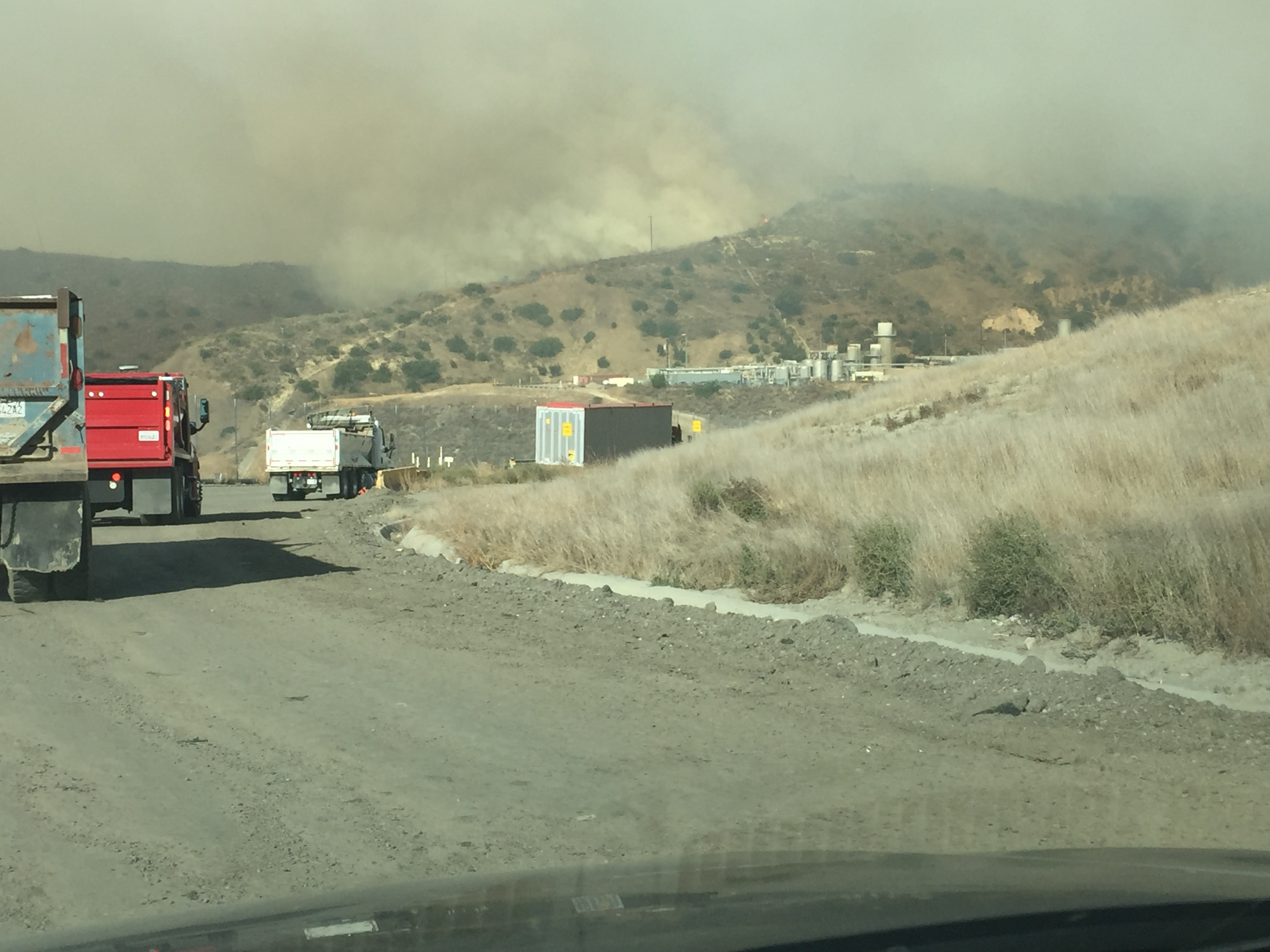 Trucks with smoke in the distance